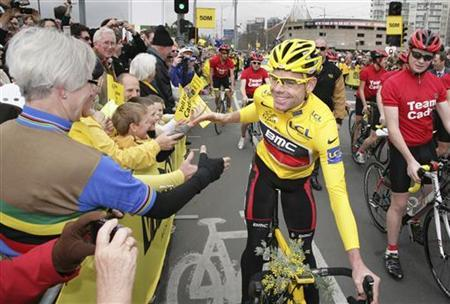Tour de France winner Cadel Evans of Australia is congratulated by fans as he rides through the streets of Melbourne to an official welcome home ceremony in Melbourne August 12, 2011. REUTERS/Brandon Malone