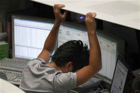 An employee of the Tokyo Stock Exchange (TSE) reacts as he works at the bourse in Tokyo August 9, 2011. REUTERS/Kim Kyung-Hoon