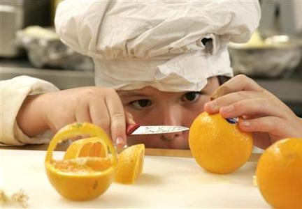 Zeke Andreassen, 11, cuts an orange into a decorative basket in the kitchen of the Vermont Kids Culinary Academy during a residential cooking summer camp in Highgate, Vermont June 19, 2012. REUTERS/Herb Swanson