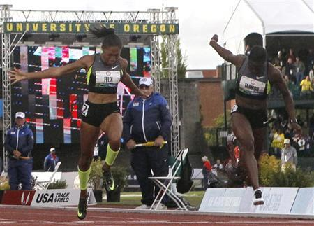 Allyson Felix (L) and Jeneba Tarmoh cross the finish line during the women's 100 meters final at the U.S. Olympic athletics trials in Eugene, Oregon, June 23, 2012. REUTERS/Lucy Nicholson