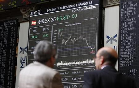 Traders look at electronic boards at the Madrid stock exchange June 22, 2012.REUTERS/Andrea Comas