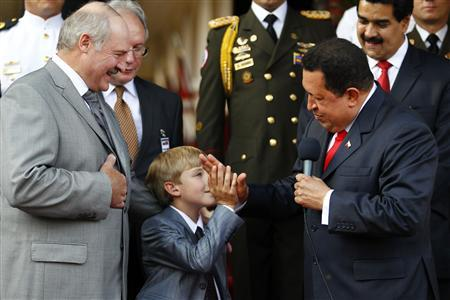 Venezuela's President Hugo Chavez (R) hi-fives Nikolay, the son of his Belarussian counterpart Alexander Lukashenko (L) at Miraflores Palace in Caracas June 26, 2012. REUTERS/Carlos Garcia Rawlins
