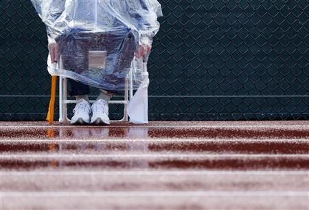 A track official waits in the rain as weather delays the women's 100m hurdles at the U.S. Olympic athletics trials in Eugene, Oregon June 23, 2012. REUTERS/Mike Blake