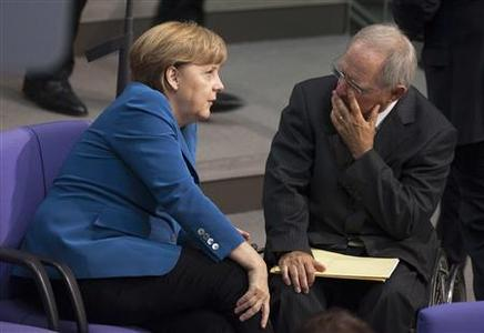 German Chancellor Angela Merkel (L) talks with Finance Minister Wolfgang Schaeuble after delivering a government policy statement at the lower house of parliament, the Bundestag, in Berlin, June 27, 2012. German Chancellor Merkel said on Wednesday, one day before a crunch European Union summit, that there were no quick or easy solutions to end the euro zone's debt crisis and leaders should avoid making rash promises they could not keep. REUTERS/Thomas Peter