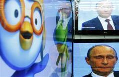 Телевизоры в московском магазине электроники транслируют общение Владимира Путина с народом 3 декабря 2009 года. Российские федеральные телеканалы, освещающие каждый шаг руководителей страны, в среду воздержались от прямой трансляции речи президента Путина в верхней палате парламента на тему политической реформы. REUTERS/Denis Sinyakov