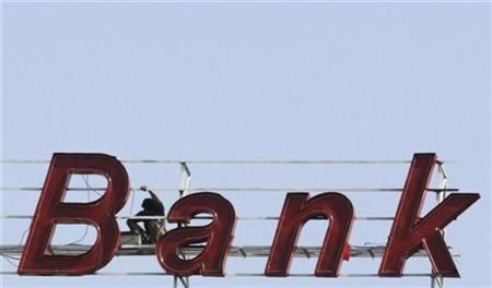 A labourer works on the sign of a bank building in the western Indian city of Ahmedabad November 26, 2010. REUTERS/Amit Dave/Files