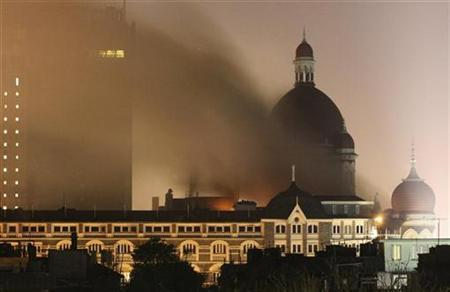 Smoke rises from the Taj Hotel in Mumbai November 27, 2008. REUTERS/Peter Keep