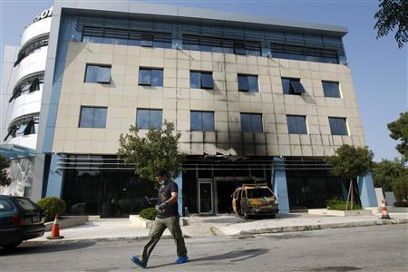 A police investigator searches for evidence following an attack on Microsoft's Greek headquarters at Marousi suburb, north of Athens June 27, 2012. Gunmen rammed a van packed with gas canisters into Microsoft's Greek headquarters in Athens and then set the vehicle on fire, causing damage but no injuries, police said on Wednesday. REUTERS/John Kolesidis