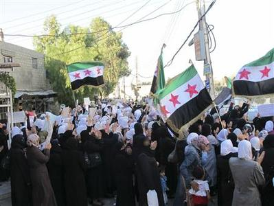 Demonstrators hold Syrian opposition flags during a protest against Syria's President Bashar al-Assad at Kfr Suseh area in Damascus June 25, 2012. Picture taken June 25, 2012. REUTERS/Shaam News Network/Handout