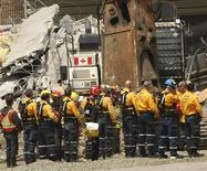 Rescue workers stand in attention as a second body is being recovered at the scene of the Algo Mall roof collapse in Elliot Lake, Ontario, June 27, 2012. REUTERS/Kenneth Armstrong
