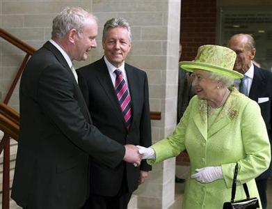 Britain's Queen Elizabeth shakes hands with Northern Ireland deputy first minister Martin McGuinness, watched by first minister Peter Robinson (C) at the Lyric Theatre in Belfast June 27, 2012. Queen Elizabeth shook the hand of former Irish Republican Army (IRA) commander McGuinness for the first time on Wednesday, drawing a line under a conflict that cost the lives of thousands of soldiers and civilians, including that of her cousin. REUTERS/Paul Faith/pool