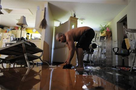 David Rivera cleans his home from the damage and water caused by floodwaters from Tropical Storm Debby in New Port Richey, Florida, June 27, 2012. REUTERS/Brian Blanco