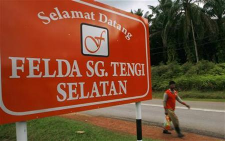 A man walks past a welcome signboard outside the Federal Land Development Authority (FELDA) Sungai Tengi Selatan palm oil plantation in Hulu Selangor, about 100 km (62 miles) north of Kuala Lumpur February 22, 2012. REUTERS/Samsul Said/Files