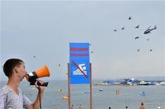 Мужчина делает объявление через мегафон на пляже во Владивостоке 21 августа 2011 года. Российская Федерация сёрфинга перенесла во Вьетнам и Индонезию этап Кубка страны из-за угрозы новых нападений акул в Приморье, сообщил в четверг представитель спортивной федерации. REUTERS/Yuri Maltsev