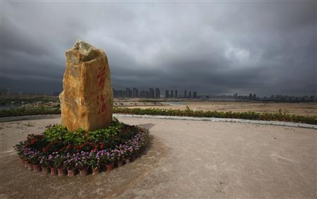 A stone bearing the Chinese name of Qianhai is displayed on top of a slope overlooking the Qianhai area in Shenzhen May 28, 2012. REUTERS/Bobby Yip