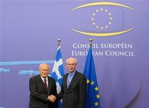 Президент Греции Каролос Папульяс (слева) пожимает руку председателю Европейского совета Херману Ван Ромпёй на встрече в Брюсселе, 27 июня 2012 года. Президент увязшей в долгах Греции полетит на саммит ЕС эконом-классом, сообщил в среду его кабинет. REUTERS/Laurent Dubrule