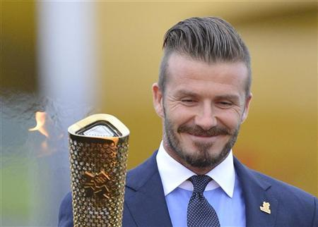 British soccer player and London 2012 Olympic Games ambassador David Beckham lights the Olympic torch with a cauldron after arriving at RNAS Culdrose base near Helston in Cornwall, south west England May 18, 2012. The London 2012 Olympic Games run from July 27 to August 12. REUTERS/Toby Melville