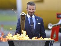 Jogador britânico e embaixador da Olimpíada de Londres, David Beckham, acende a tocha olímpica em caldeirão na base RNAS de Culdrose em Cornwall, sudoeste da Inglaterra. David Beckham não foi convocado para a seleção olímpica de futebol da Grã-Bretanha. 18/05/2012 REUTERS/Toby Melville