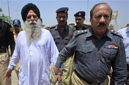 A police official escorts Indian prisoner Surjeet Singh (L) at Wagah border before crossing into India after his release from the Kotlakhpat jail in Lahore June 28, 2012. REUTERS/Mohsin Raza