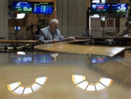 A trader looks at data sheets at the Madrid stock exchange June 18, 2012. REUTERS/Paul Hanna