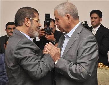 The Muslim Brotherhood's President-elect Mohamed Mursi (L) shakes hand with Egyptian political Dr.Abdel Gelil Mostafa at the presidential palace in Cairo June 27, 2012. REUTERS/Egyptian Presidency/Handout