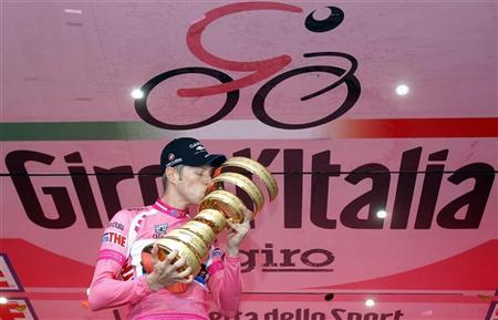 Pink jersey holder and overall leader Garmin-Barracuda's Ryder Hesjedal of Canada kisses the trophy on the podium after the 28.2km (17 miles) time trial in the 21st and last stage of the Giro d'Italia cycling race in Milan, May 27, 2012. REUTERS/Alessandro Garofalo