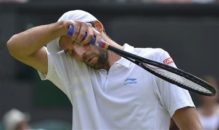 Ivo Karlovic of Croatia wipes his face during his men's singles tennis match against Andy Murray of Britain at the Wimbledon tennis championships in London June 28, 2012. REUTERS/Toby Melville