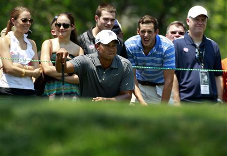 Fans watch as Tiger Woods (C) of the U.S. lines up a putt during the first round of the AT&T National golf tournament at Congressional Country Club in Bethesda, Maryland June 28, 2012. REUTERS/Kevin Lamarque