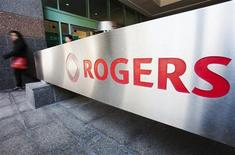 A woman walks by a sign at the Rogers Communications headquarters building on the day of their annual general meeting for shareholders in Toronto, April 25, 2012. REUTERS/Mark Blinch