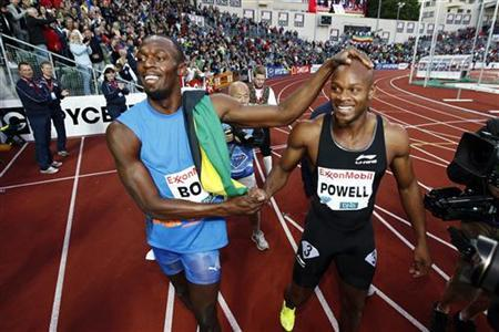Usain Bolt (L) and Asafa Powell of Jamaica celebrate after Bolt won the men's 100m at the IAAF Diamond League athletics meeting at Bislett Stadium in Oslo June 7, 2012. REUTERS/Heiko Junge/Scanpix
