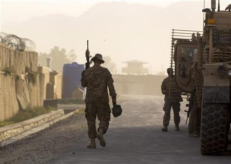 A soldier from the 4th Brigade Combat Team, 4th Infantry Division walks with his weapon to an MRAP while preparing to leave in a convoy inside FOB Joyce in Afghanistan's Kunar Province June 24, 2012. REUTERS/Lucas Jackson