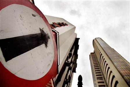 A road sign stands next to the Bombay Stock Exchange building (R) in this August 3, 2005 file photo. REUTERS/Arko Datta/Files