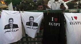 "A boy stands near t-shirts with images of elected president Mohamed Mursi and words that read ""Congratulations to Egypt"" that are sold during a sit-in against the military council and the decision to dissolve parliament, at Tahrir Square in Cairo June 28, 2012. REUTERS/Amr Abdallah Dalsh"
