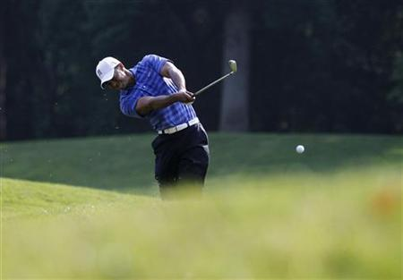 Tiger Woods of the U.S. plays his second shot on the 14th hole during the second round of the AT&T National golf tournament in Bethesda, Maryland June 29, 2012. REUTERS/Jason Reed