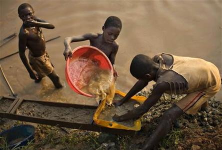 Boys pan for gold on a riverside at Iga Barriere, 25 km (15 miles) from Bunia, in the resource-rich Ituri region of eastern Congo February 16, 2009. REUTERS/Finbarr O'Reilly/Files