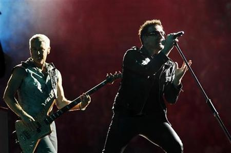 Lead singer Bono of Irish rock band U2 performs with Adam Clayton (L) during their 360 Degree Tour at King Baudouin Stadium in Brussels September 22, 2010. REUTERS/Thierry Roge
