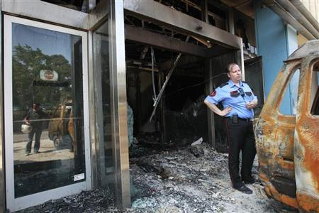 A security guard stands near a damaged van outside the burnt entrance of Microsoft's Greek headquarters following an attack at Marousi suburb, north of Athens June 27, 2012. REUTERS/John Kolesidis