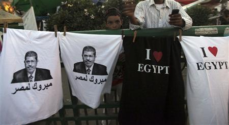 A boy stands near t-shirts with images of elected president Mohamed Mursi and words that read ''Congratulations to Egypt'' that are sold during a sit-in against the military council and the decision to dissolve parliament, at Tahrir Square in Cairo June 28, 2012. REUTERS/Amr Abdallah Dalsh