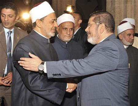 Egypt's President-elect Mohamed Mursi (R) shakes hand with Grand Sheikh of al-Azhar Ahmed El-Tayeb before Friday prayers at al-Azhar mosque, in the old quarter of Cairo June 29, 2012. Muslim Brotherhood supporters flocked to Cairo's Tahrir Square on Friday to hear Mursi speak on the eve of his inauguration as Egypt's first Islamist, civilian president. REUTERS/Egyptian Presidency/Handout