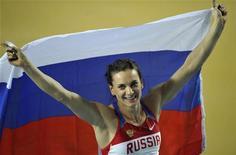A medalhista de ouro russa Elena Isinbayeva levanta sua bandeira nacional em um campeonato na arena Atakoy Athletics em Istanbul, na Turquia. Yelena voltou a competir no auge de sua capacidade para tentar se tornar a primeira mulher a conquistar três medalhas de ouro olímpicas nos Jogos de Londres, que podem ser os seus últimos. 11/03/2012 REUTERS/Dylan Martinez
