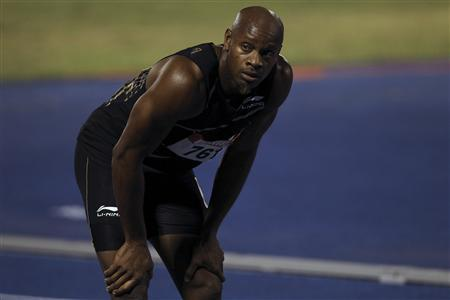 Asafa Powell (L) takes a break after the men's 100 meters quarters-final heats at the Jamaican Olympic trials in Kingston city June 28, 2012. REUTERS/Ivan Alvarado