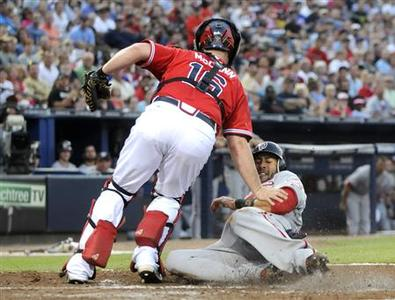 Washington Nationals runner Michael Morse slides in safe past Atlanta Braves catcher Brian McCann in the third inning at their MLB National League baseball game at Turner Field in Atlanta, Georgia June 29, 2012. REUTERS/Tami Chappell