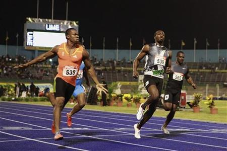 Yohan Blake (L) and Usain Bolt (front R) cross the finish line during their men's 100 meters final event at the Jamaican Olympic trials in Kingston city, June 29, 2012. REUTERS/Gilbert Bellamy