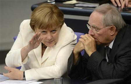 German Chancellor Angela Merkel (L) talks with her Finance Minister Wolfgang Schaeuble before the vote for ratification of the European Union fiscal pact in the Reichstag, the seat of the German lower house of parliament, the Bundestag, in Berlin, June 29, 2012. REUTERS/Fabian Bimmer