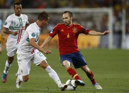 Portugal's Joao Pereira and Spain's Andres Iniesta (R) fight for the ball during their Euro 2012 semi-final soccer match at the Donbass Arena in Donetsk, June 27, 2012. REUTERS/Eddie Keogh
