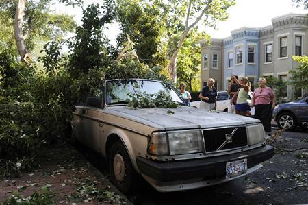People survey storm damage in the Capitol Hill neighborhood in Washington, June 30, 2012. Wind gusts clocked at speeds of up to 79 mph were reported in and around the U.S. capital, knocking out power to hundreds of thousands of homes in the Washington area. REUTERS/Jonathan Ernst