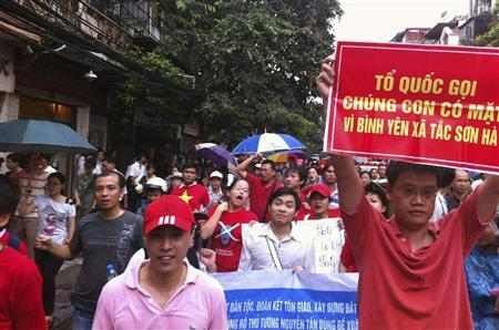 Protesters hold anti-China banners while marching during an anti-China protest along a street in Hanoi July 1, 2012. The banner (R) reads as ''The Nation! We stand ready for peace... since your call!'' REUTERS/Stringer