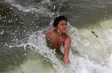 A boy plays in the ocean at Coney Island in the Brooklyn borough of New York June 30, 2012. Nearly 4 million homes and businesses were without power on Saturday amid a record heat wave in the eastern United States after deadly thunderstorms downed power lines from Indiana to New Jersey. REUTERS/Eric Thayer