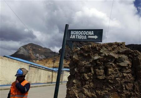 A miner stands next to a sign at the Morococha town in the Andes May 13, 2010. REUTERS/Pilar Olivares