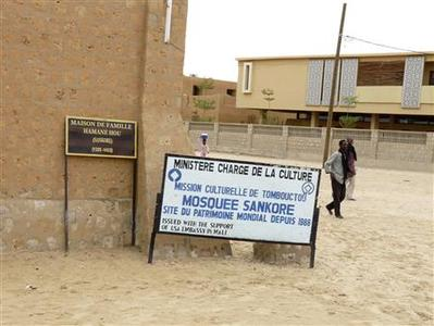 People walk past signs marking heritage sites in the Malian city of Timbuktu May 15, 2012. Al Qaeda-linked Mali Islamists armed with Kalashnikovs and pick-axes began destroying prized mausoleums of saints in the UNESCO-listed northern city of Timbuktu on June 30, 2012 in front of shocked locals, witnesses said. The Islamist Ansar Dine group backs strict sharia, Islamic law, and considers the shrines of the local Sufi version of Islam idolatrous. Sufi shrines have also been attacked by hardline Salafists in Egypt and Libya in the past year. Picture taken May 15, 2012. REUTERS/Adama Diarra